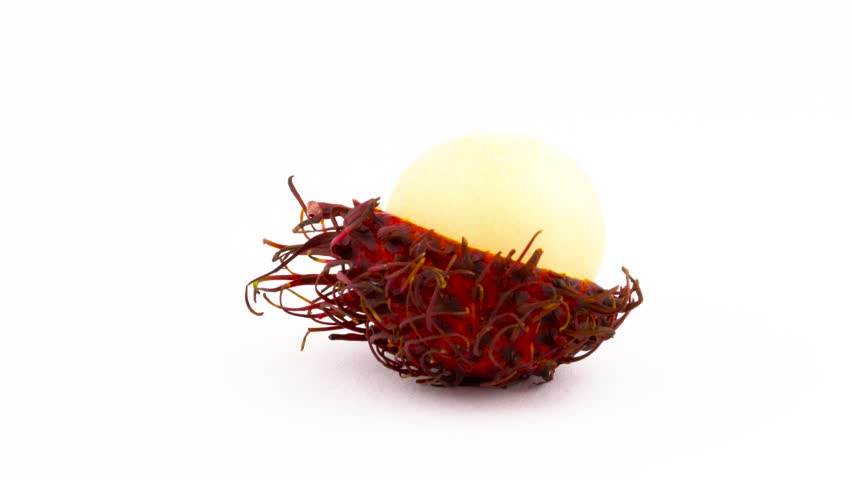 One half peeled red color rambutan fruit. Rotating on the turntable isolated on the white background. Close up. Macro.