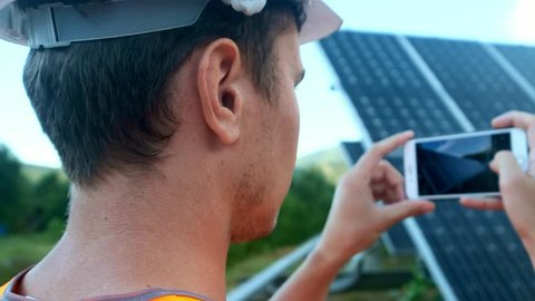 Engineer expert in solar energy photovoltaic panels with remote control performs routine actions for system monitoring using clean, renewable energy. Makes photos of solar panels on a smartphone