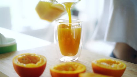 Pouring fresh orange juice from glass jar into glass. Squeezed orange parts on wooden board. Close up glass of fresh orange juice. Healthy and vegetarian diet. Fruit beverage on kitchen table