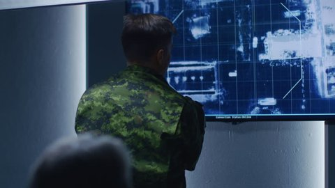 Military Man / Army Officer Watches Satellite Surveillance Footage / Car Tracking of the Target on Wall TV Screen. Secret Military Spying Operation. Shot on RED EPIC-W 8K Helium Cinema Camera.