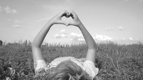 Love and happiness concept. Cute white child forming heart gesture with hands isolated at sky outdoors while laying on back in grass in rural landscape. Real time black and white video footage.