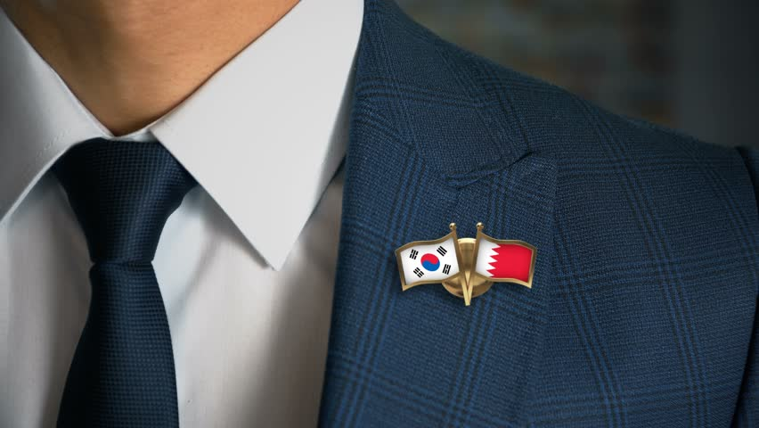 Businessman Walking Towards Camera With Friend Country Flags Pin South Korea - Bahrain