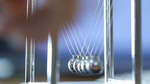 Newton's cradle office toy. Slow motion. a pendulum with swinging metal spheres demonstrates conservation of momentum