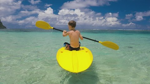 Boy paddling canoe on a tropical lagoon with coral reef