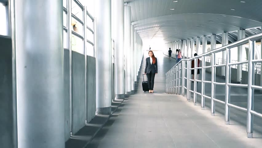 Young attractive Asian business woman dragging a wheeled suitcase at the airport ramp way for business trip | Shutterstock HD Video #1015451428