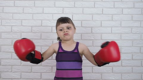 Child in the boxing rack. Little girl in boxing gloves.