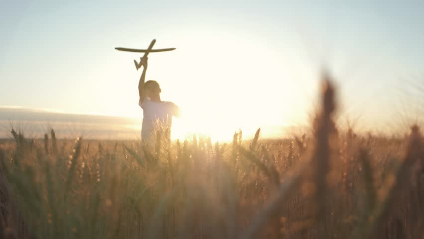 Happy child runs with a toy airplane on a sunset background over a field. The concept of a happy family. Childhood dreams | Shutterstock HD Video #1015465378