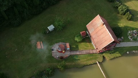 Hot water tub in yard  near wooden bathhouse, aerial view