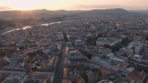 Aerial view of downtown Budapest and the Danube river with bridges in sunset - drone video