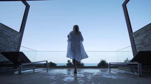 A blond girl in a white bathrobe walks out onto the balcony. Back view. Seaview.