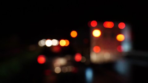 Urban scene with bokeh emergency lights and blurred stationary cars on the road at night