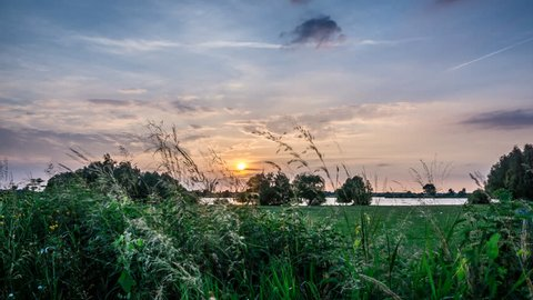 Sunset near Asselt, in the southern province of Limburg, The Netherlands, Europe. Time lapse footage with moving clouds and a flock of geese in a meadow.