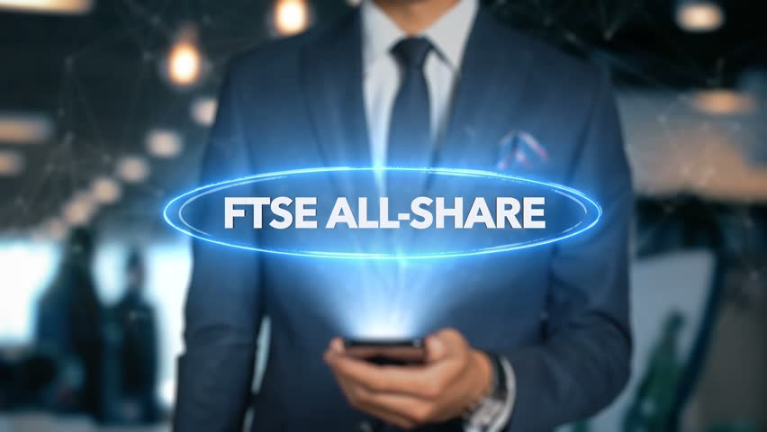 Businessman With Mobile Phone Opens Hologram HUD Interface and Touches Word - FTSE ALL-SHARE