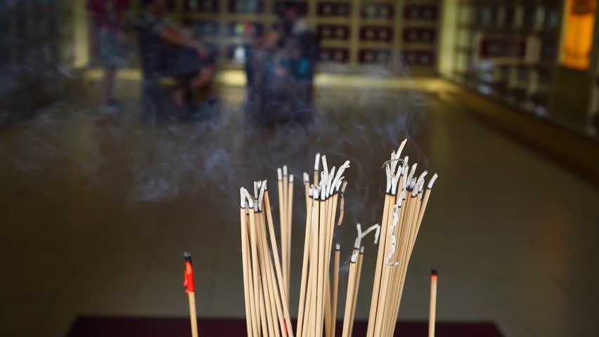 burning joss sticks inside temple