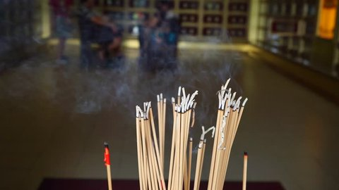 burning joss sticks inside temple