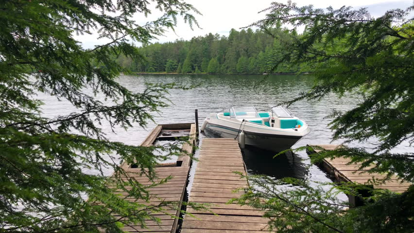 Ski Boat at Dock on Forested Lake | Shutterstock HD Video #1015530118
