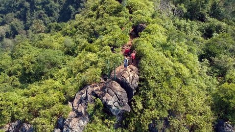 Drone footage of people are climbing mountains in a forest in Ha Long Bay, Cat Ba Island, Vietnam.