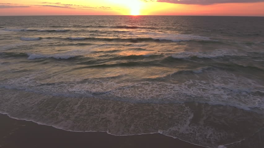 This is a video of a drone flying along the beach looking out at the waves and the ocean during sunrise.