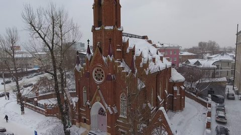Winter Church of Our Lady of the Assumption catolic religion tourist attraction in center of Irkutsk. Cold Siberia snow old city. Aerial flight close