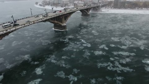 Flight above Angara river Irkutsk city sightseeing panorama. Center main arc bridge day car road traffic. Russia Extreme cold winter snow blizzard weather.  Aerial drone cinematic drift
