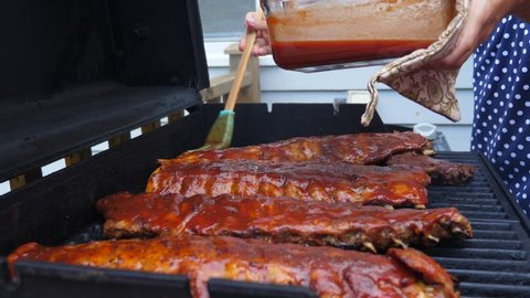 Amazing and delicious racks of ribs cooking on a hot and smokey barbecue