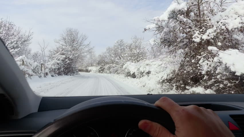 winter driving POV - snowy country road driving in winter - snowy country road. View from the driver angle while hands on the wheel