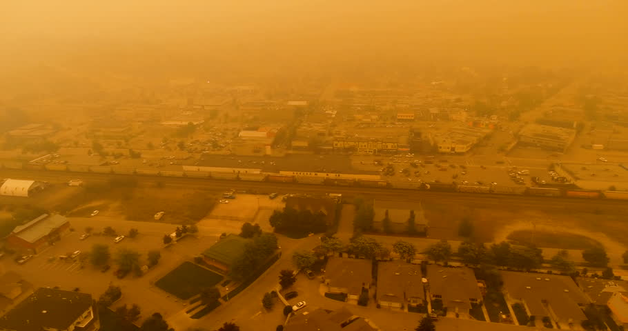 Tracking aerial drone shot of BC rail train traveling through thick Canadian wildfire smoke through small city in the okanagan - Central interior of British Columbia | Shutterstock HD Video #1015580728