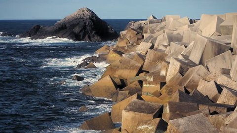 Cudillero, Asturias, Spain. View of the port's breakwater made out of huge square dices.