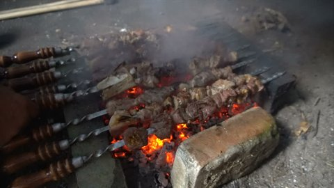Marinated shashlik preparing on a barbecue grill over charcoal. Shashlik or Shish kebab popular in Eastern Europe. Shashlyk (skewered meat) was originally made of lamb. Roast Beef Kebabs On BBQ Grill