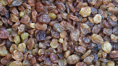 Pile raisins background, close up rotation 4k top view. Food  background. Gastronomy concept, organic food. Macro dry raisins