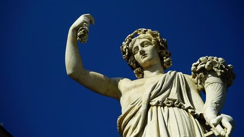 view of marble statue with cornucopia from below with blue sky