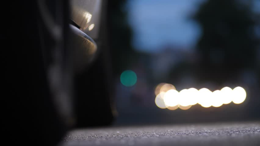 Car's door opens, woman's legs in sexy high heels stiletto shoes stepping out of automobile in night city and walking to camera. Female in high heels getting out of car on bokeh lights background