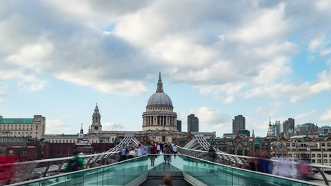 Time lapse view of the Millennium bridge in London with St Paul cathedral and tourists and commuters walking