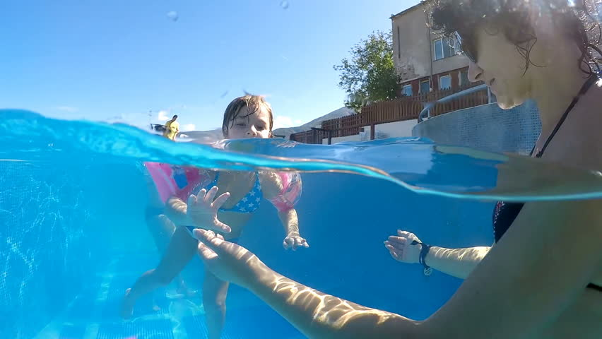 Little girl with Inflatable armbands swimming toward mother in thermal water spa pool, SLOW MOTION half underwater shot