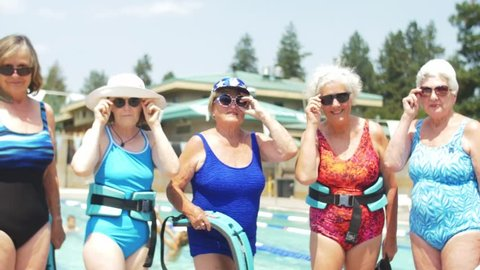Five adorable old ladies wearing festive bathing suits stand by the pool, and flirtaciously lower and raise their sunglasses at the camera