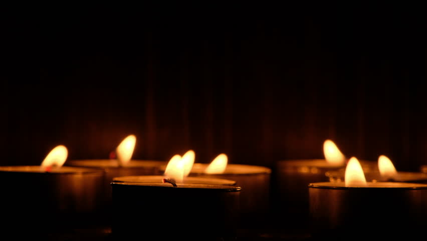 Lit candle tealights against dark background