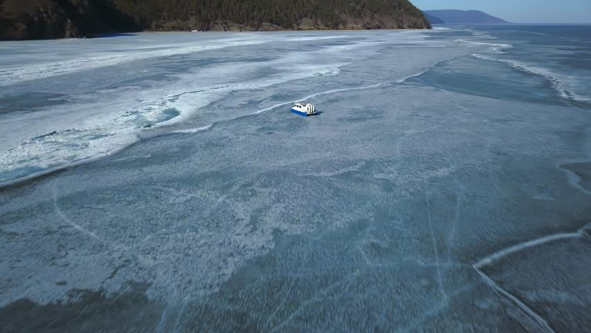 Hovercraft boat on ice of Baikal lake. Aerial view.