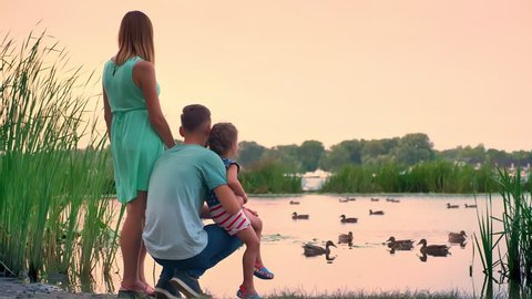Silhouette of young family is walking in summer, sunset, watching ducks on lake, nature concept, relax concept