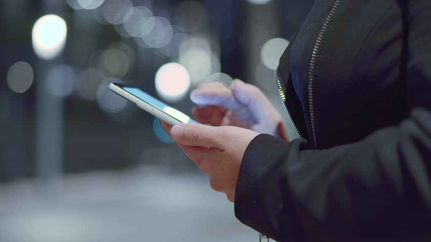 Women's hands holding cell phone with bright screen | Shutterstock HD Video #1015684768