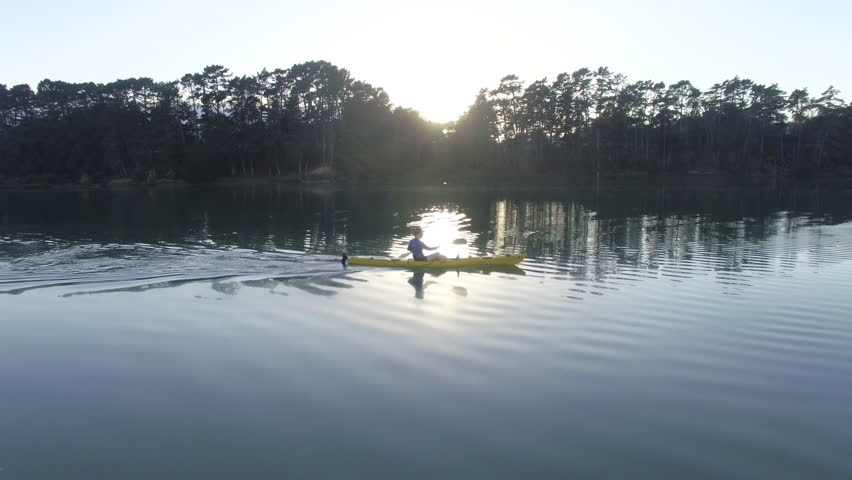 Aerial shot following solo kayaker in yellow kayak paddling on reflective water at sunrise with sun in the background in New Zealand | Shutterstock HD Video #1015687048