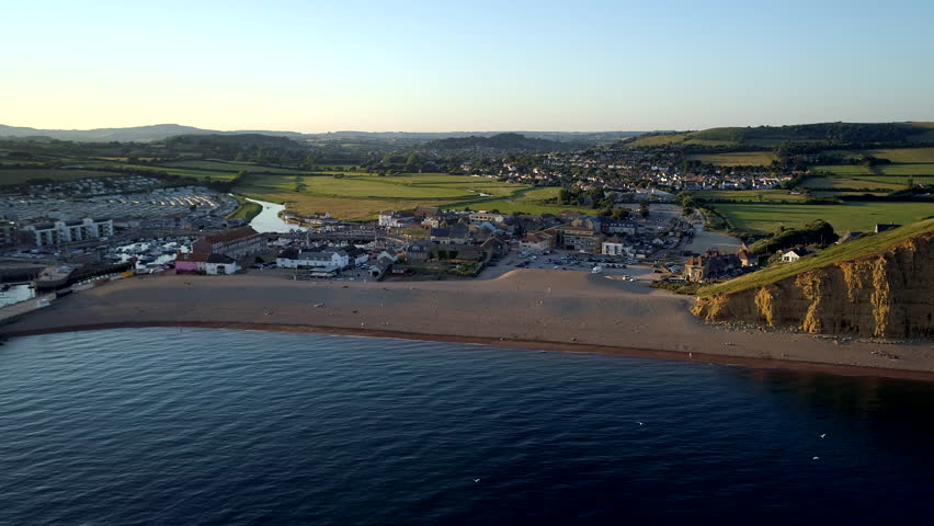 Drone flies slowly towards beach of West Bay in Dorset during sunset. Bridport and Dorset countryside in background