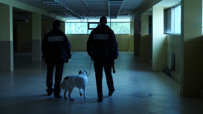 Security guards with dog inspect big hall slow motion shot