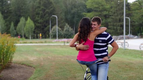 HD A couple is sitting on one bycicle looking at each other and hugs