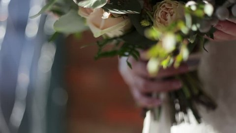 Beautiful bridal bouquet in hands of young bride dressed in white wedding dress. Bride hand touching the wedding bouquet. Close up of big bunch of fresh white roses and tulips flowers in female hands