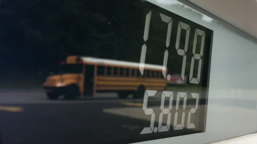 A detailed close-up view of a gas pump's meter with traffic passing by in the reflection.