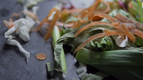Scraps leftover from cutting raw salad from carrots, cabbage, lettice, cucumber over large wooden cutting board