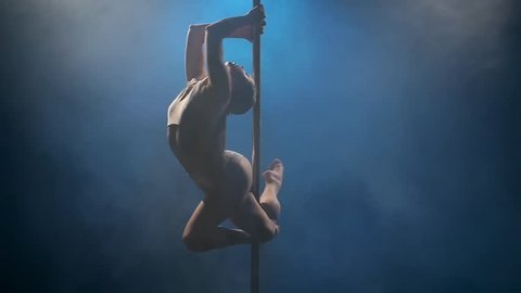 Dancer in a dark studio spins on a pole in blue smoke . Blue smoke background. Slow motion