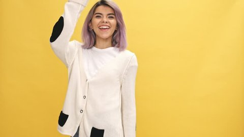 Smiling woman in warm cardigan walking and meets someone over yellow background