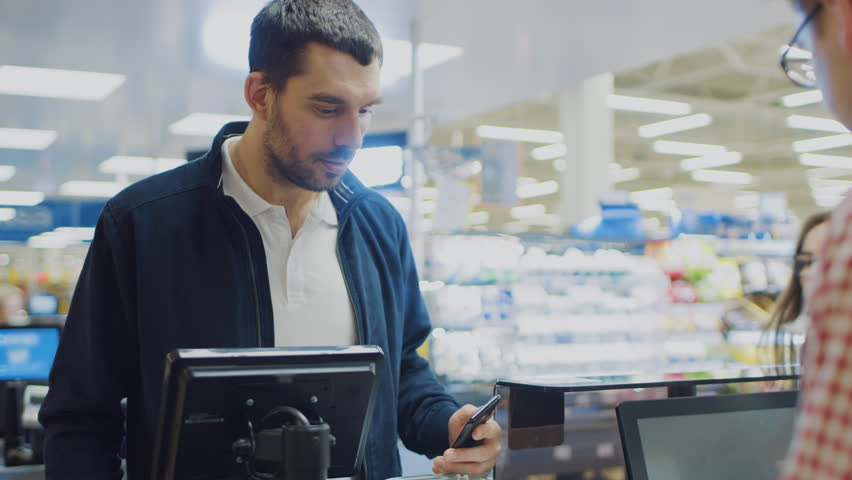 At the Supermarket: Checkout Counter Customer Pays with Smartphone for His Food Items. Big Shopping Mall with Friendly Cashier, Small Lines and Modern Wireless Paying Terminal System. | Shutterstock HD Video #1015778248