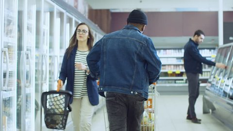 At the Supermarket: Happy Stylish Guy Pushes Shopping Cart and Chooses Products in the Frozen Goods Section of the Store. Big Mall with Glass Door Fridge. Shot on RED EPIC-W 8K Helium Cinema Camera.